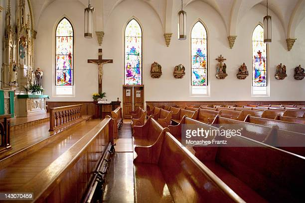 pews and stained glass windows in church - katholicisme stockfoto's en -beelden