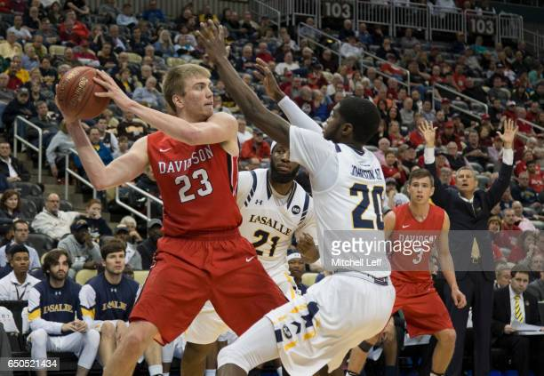 Peyton Aldridge of the Davidson Wildcats controls the ball against BJ Johnson and Jordan Price of the La Salle Explorers in the second round of the...