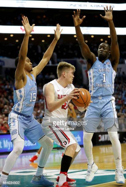 Peyton Aldridge of the Davidson Wildcats is trapped by teammates Garrison Brooks and Theo Pinson of the North Carolina Tar Heels during their game at...