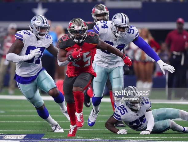 Peyton Barber of the Tampa Bay Buccaneers breaks away from Taco Charlton Randy Gregory and of the Dallas Cowboys in the third quarter at ATT Stadium...