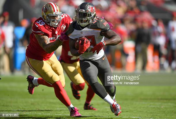 Peyton Barber of the Tampa Bay Buccaneers carries the ball while pursued by Aaron Lynch of the San Francisco 49ers during the second quarter of an...
