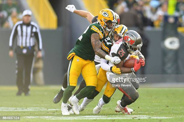 Peyton Barber of the Tampa Bay Buccaneers is brought down by Josh Jones of the Green Bay Packers during the first half at Lambeau Field on December 3...
