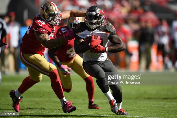 Peyton Barber of the Tampa Bay Buccaneers is grabbed by Aaron Lynch of the San Francisco 49ers during their NFL game at Levi's Stadium on October 23...
