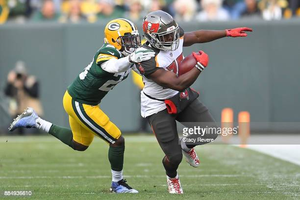 Peyton Barber of the Tampa Bay Buccaneers is pursued by Josh Jones of the Green Bay Packers during the first half at Lambeau Field on December 3 2017...