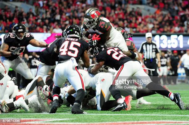 Peyton Barber of the Tampa Bay Buccaneers jumps over the pile to score a touchdown during the second half against the Atlanta Falcons at MercedesBenz...
