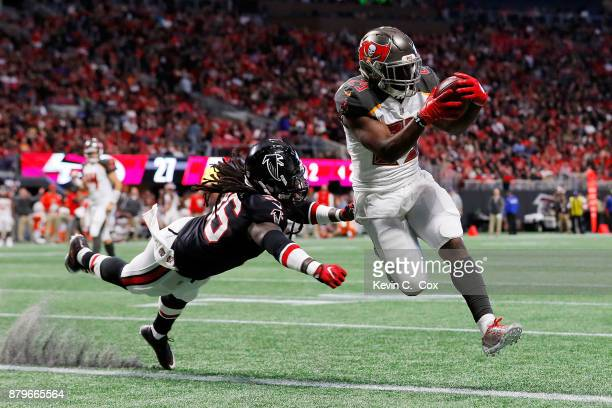 Peyton Barber of the Tampa Bay Buccaneers runs into the end zone for a touchdown past Kemal Ishmael of the Atlanta Falcons during the second half at...