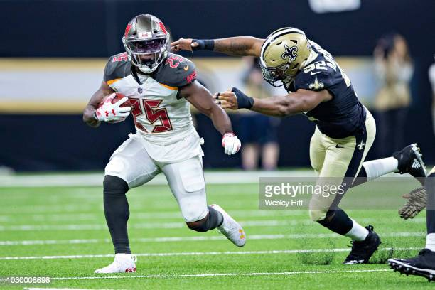 Peyton Barber of the Tampa Bay Buccaneers runs the ball past the out stretch arms of Marcus Davenport of the New Orleans Saints at MercedesBenz...