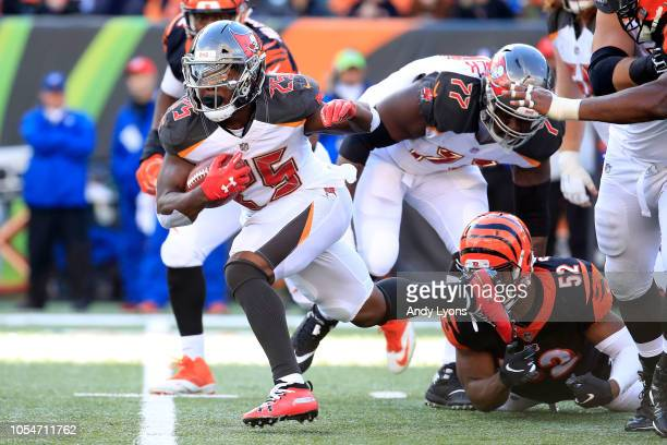 Peyton Barber of the Tampa Bay Buccaneers slips out of a tackle by Preston Brown of the Cincinnati Bengals during the fourth quarter at Paul Brown...