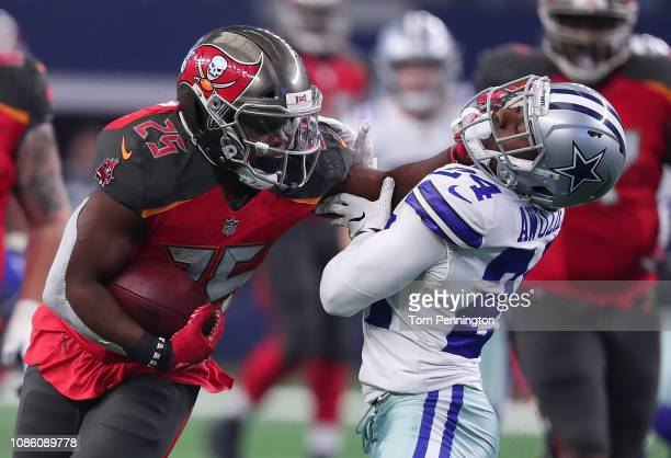 Peyton Barber of the Tampa Bay Buccaneers stiff arms Chidobe Awuzie of the Dallas Cowboys on a carry in the third quarter at ATT Stadium on December...
