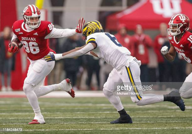 Peyton Hendershot of the Indiana Hoosiers gives the stiff arm as Josh Uche of the Michigan Wolverines reaches for the tackle during the first half at...