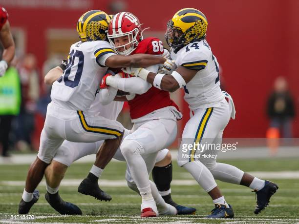 Peyton Hendershot of the Indiana Hoosiers runs the ball after a reception as Daxton Hill of the Michigan Wolverines and Josh Metellus of the Michigan...