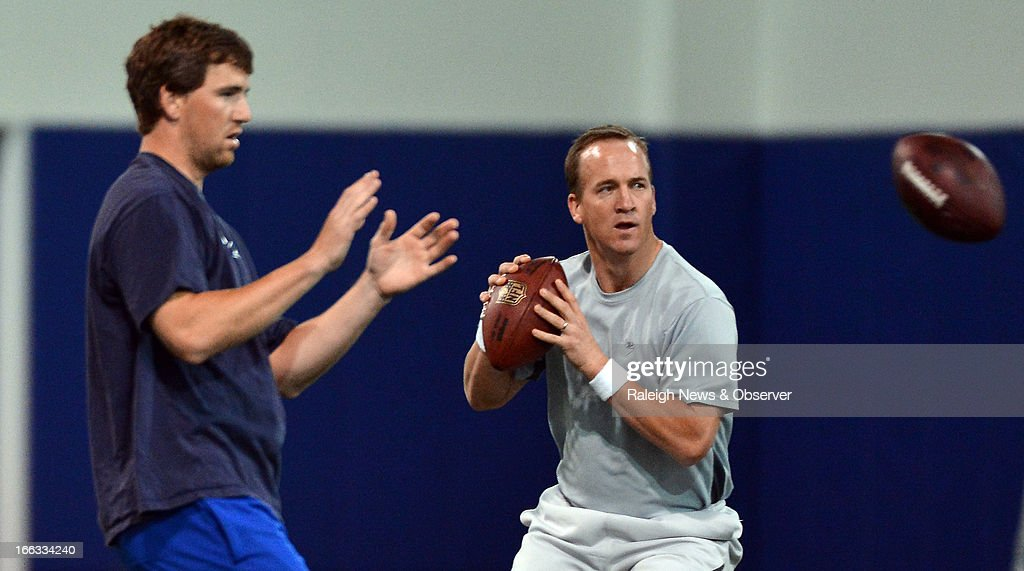 Peyton Manning and his brother Eli run through drills during a workout at Duke's Pascal Field House in Durham, North Carolina, Thursday, April 11, 2013.