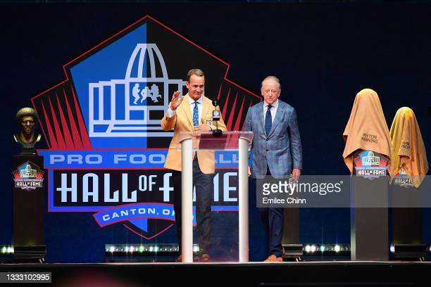 Peyton Manning greets the crowd with his father Archie Manning during the NFL Hall of Fame Enshrinement Ceremony at Tom Benson Hall Of Fame Stadium...