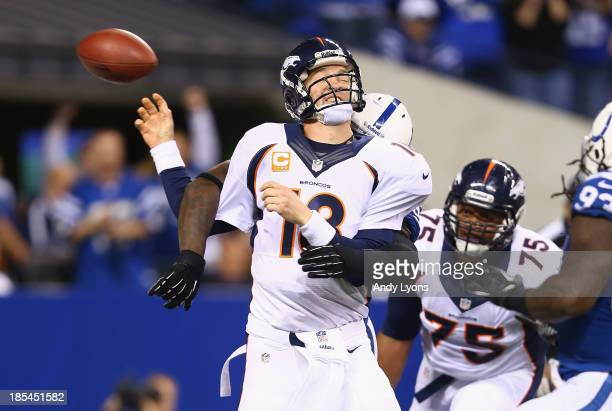 Peyton Manning of the Denver Broncos fumbles the ball as he is hit during the game against the Indianapolis Colts at Lucas Oil Stadium on October 20...