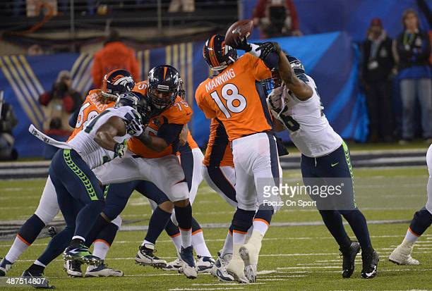 Peyton Manning of the Denver Broncos gets his pass off under pressure from Cliff Avril of the Seattle Seahawks during Super Bowl XLVIII on February 2...
