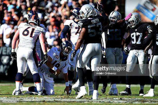 Peyton Manning of the Denver Broncos gets off the ground after being sacked by Benson Mayowa of the Oakland Raiders during the second half of the...
