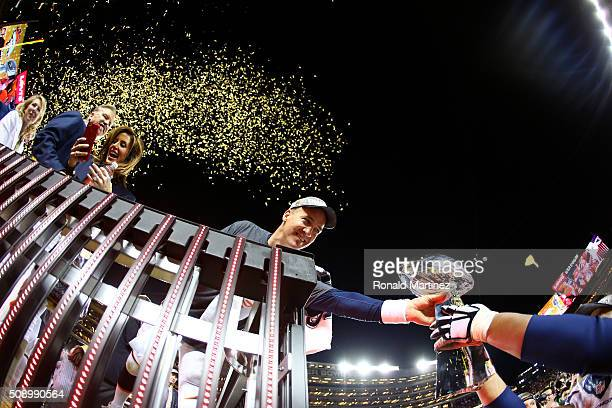 Peyton Manning of the Denver Broncos is handed the Vince Lombardi Trophy after defeating the Carolina Panthers during Super Bowl 50 at Levi's Stadium...
