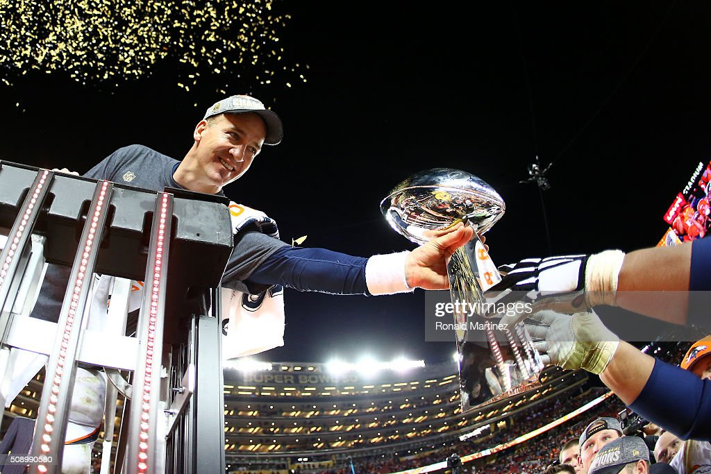 Peyton Manning #18 of the Denver Broncos is handed the Vince Lombardi Trophy after defeating the Carolina Panthers during Super Bowl 50 at Levi's Stadium on February 7, 2016 in Santa Clara, California. The Broncos defeated the Panthers 24-10.