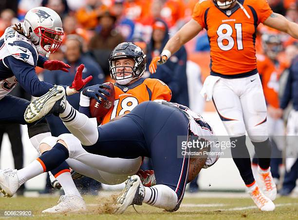 Peyton Manning of the Denver Broncos is sacked in the second quarter by Alan Branch of the New England Patriots in the AFC Championship game at...