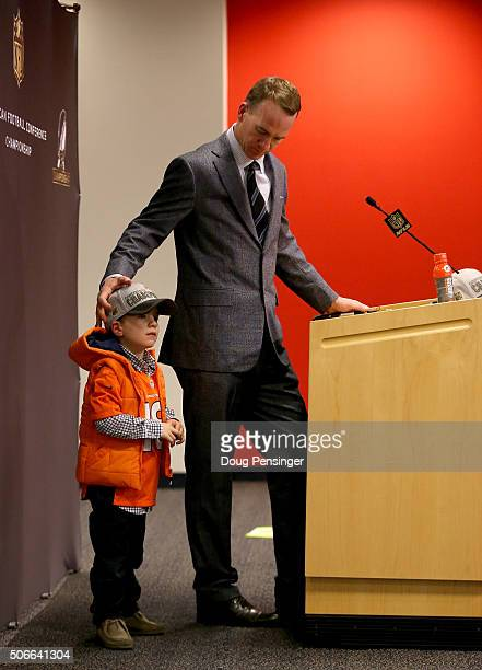 Peyton Manning of the Denver Broncos looks on with his son Marshall Manning during a post game press conference after defeating the New England...
