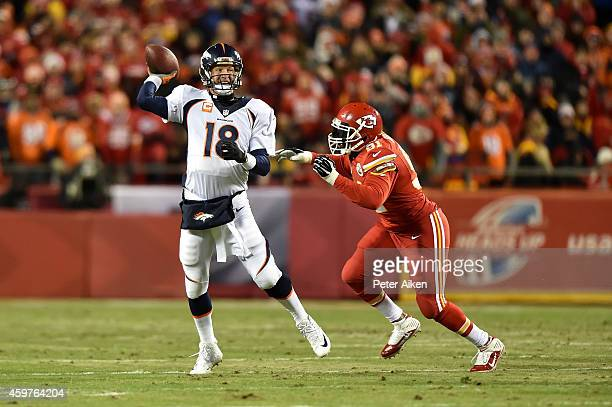 Peyton Manning of the Denver Broncos passes against Tamba Hali of the Kansas City Chiefs during the first half at Arrowhead Stadium on November 30...