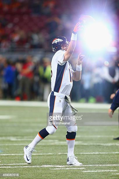 Peyton Manning of the Denver Broncos passes during warmups as a camera flash lights up in the background prior to playing against the St Louis Rams...