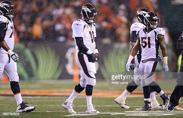 Peyton Manning of the Denver Broncos walks off of the field after throwing an interception to Dre Kirkpatrick of the Cincinnati Bengals during the...