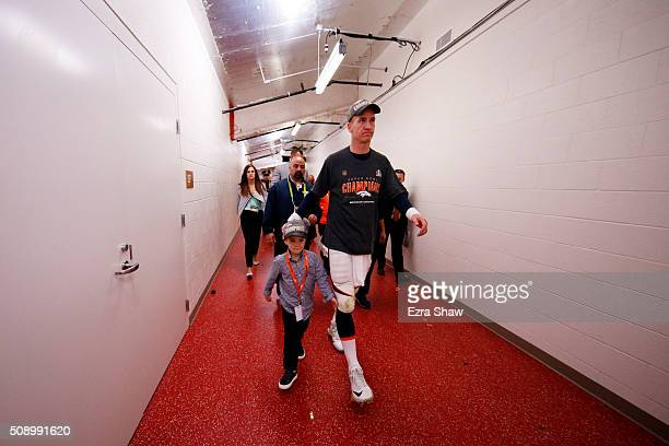 Peyton Manning of the Denver Broncos walks with his son Marshall Manning after defeating the Carolina Panthers during Super Bowl 50 at Levi's Stadium...