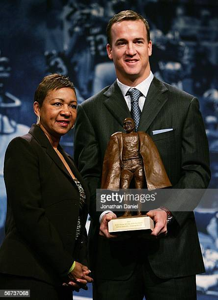 Peyton Manning of the Indianapolis Colts and Connie Payton wife of deceased star Walter Payton hold the Walter Payton Man of the Year trophy during a...