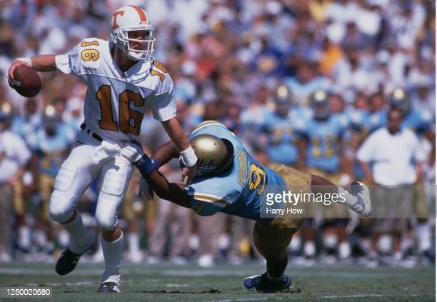 Peyton Manning, Quarterback for the University of Tennessee Volunteers avoids the tackle by Defensive Linebacker Weldon Forte of the University of...