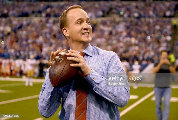 Peyton Manning steps back to throw a pass to former teammate Marvin Harrison during a presentation to retire Manning's number during the halftime of...