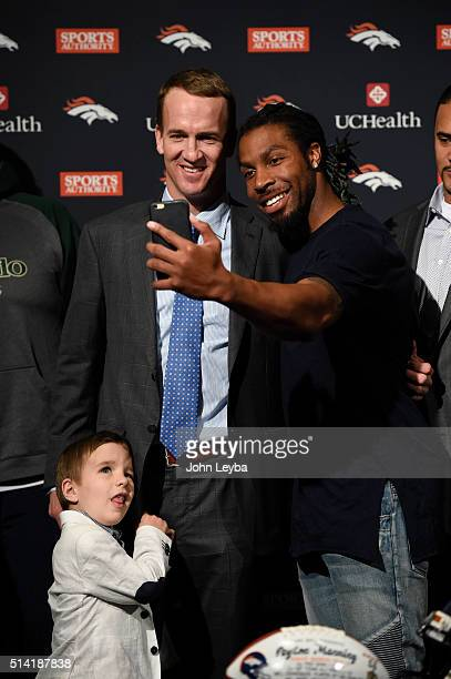 Peyton Manning takes a selfie with David Bruton as Manning's son Marshall stands below after his press conference The Denver Broncos hold a press...