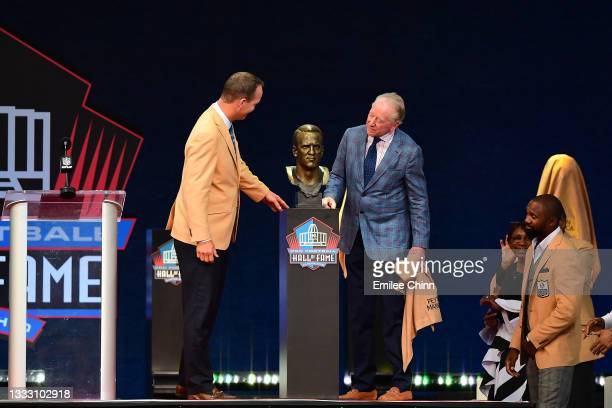 Peyton Manning unveils his bust with his father Archie Manning during the NFL Hall of Fame Enshrinement Ceremony at Tom Benson Hall Of Fame Stadium...