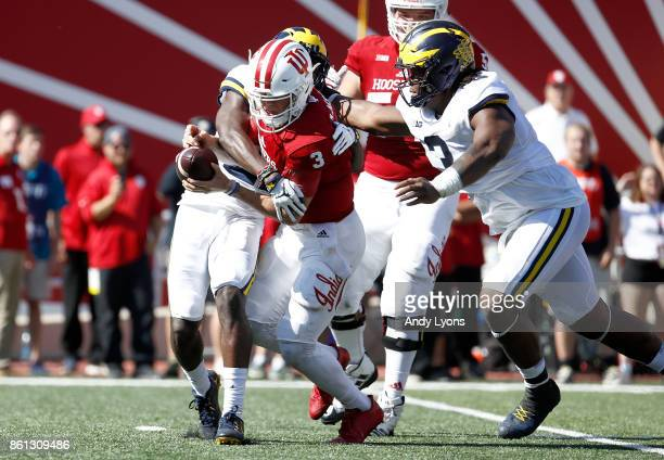 Peyton Ramsey of the Indiana Hoosiers is sacked by David Long and Brad Robbins of the Michigan Wolverines during the game at Memorial Stadium on...