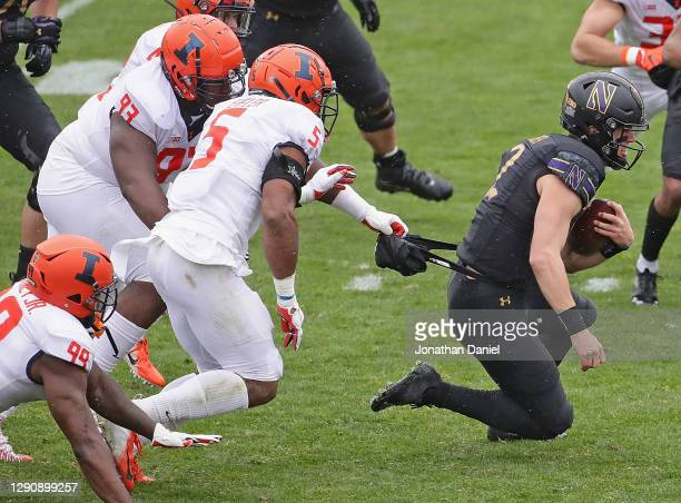 Peyton Ramsey of the Northwestern Wildcats is pulled down by the hand warmer by Calvin Avery of the Illinois Fighting Illini at Ryan Field on...