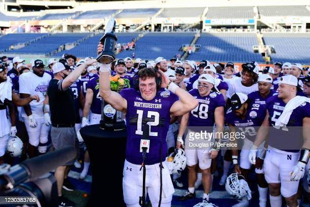 Peyton Ramsey of the Northwestern Wildcats raises the MVP trophy after defeating the Auburn Tigers to win the Vrbo Citrus Bowl at Camping World...
