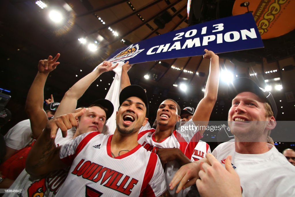 Peyton Siva (C, foreground) #3 and Wayne Blackshear #20 (holding sign) of the Louisville Cardinals celebrate with teammates after they won 78-61 against the Syracuse Orange during the final of the Big East Men's Basketball Tournament at Madison Square Garden on March 16, 2013 in New York City.