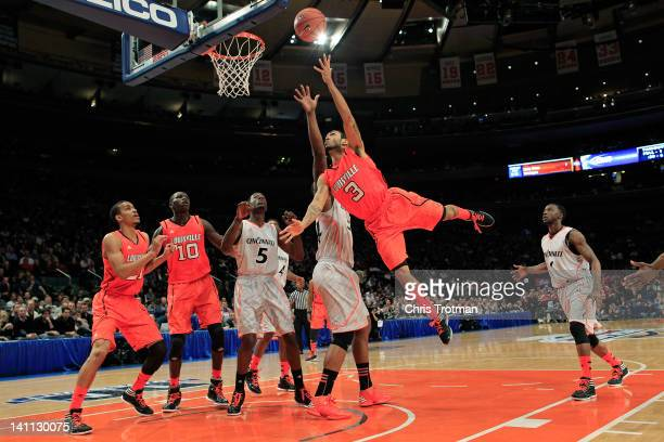 Peyton Siva of the Louisville Cardinals goes to the hoop against Yancy Gates of the Cincinnati Bearcats during the finals of the Big East Men's...