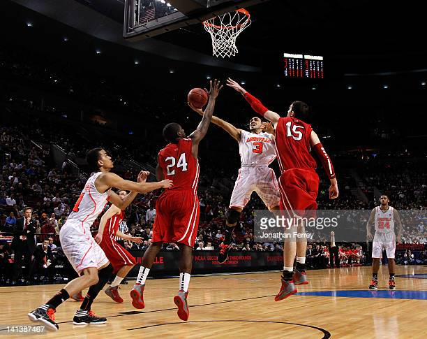 Peyton Siva of the Louisville Cardinals goes up for a shot between De'Mon Brooks and Jake Cohen of the Davidson Wildcats in the second half in the...