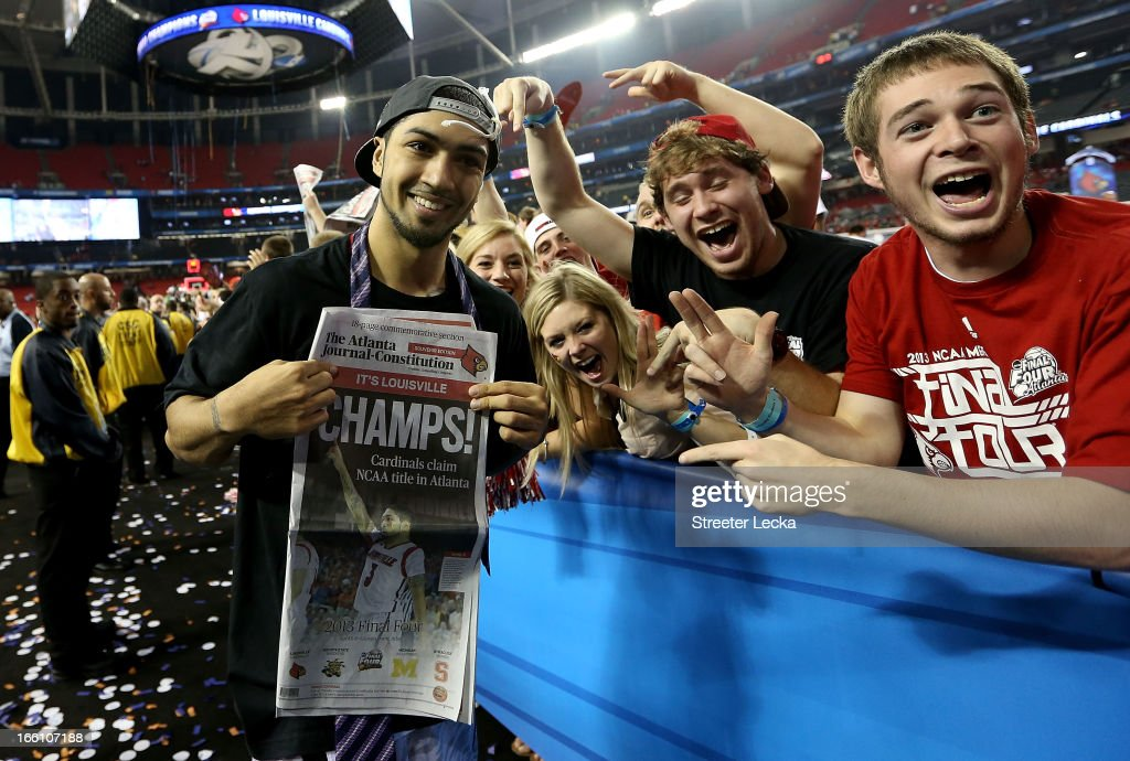 Peyton Siva #3 of the Louisville Cardinals holds up a newspaper which reads 'Champs' as he celebrates with fans after Louisville won 82-76 against the Michigan Wolverines during the 2013 NCAA Men's Final Four Championship at the Georgia Dome on April 8, 2013 in Atlanta, Georgia.