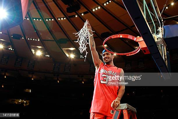 Peyton Siva of the Louisville Cardinals holds up the net after cutting it down after defeating the Cincinnati Bearcats during the finals of the Big...