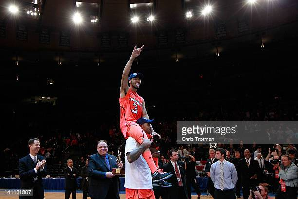 Peyton Siva of the Louisville Cardinals is carried on a teammates shoulders prior to receiving his MVP trophy after defeating the Cincinnati Bearcats...