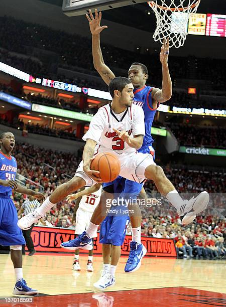 Peyton Siva of the Louisville Cardinals passes the ball while defended by Cleveland Melvin of the DePaul Blue Demons during the Big East Conference...