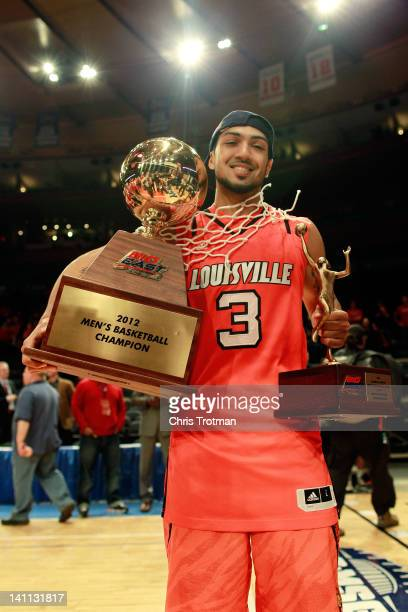 Peyton Siva of the Louisville Cardinals poses with the trophy, his mvp trophy and the net after defeating the Cincinnati Bearcats during the finals...