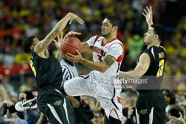Peyton Siva of the Louisville Cardinals with the ball between Demetric Williams and Fred VanVleet of the Wichita State Shockers in the first half...