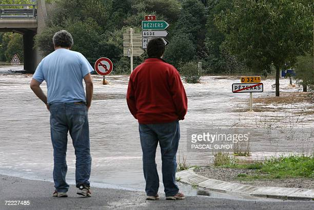 People look at a flooded road following heavy rain over the region 20 October 2006 in Pezenas southwestern France AFP PHOTO PASCAL GUYOT