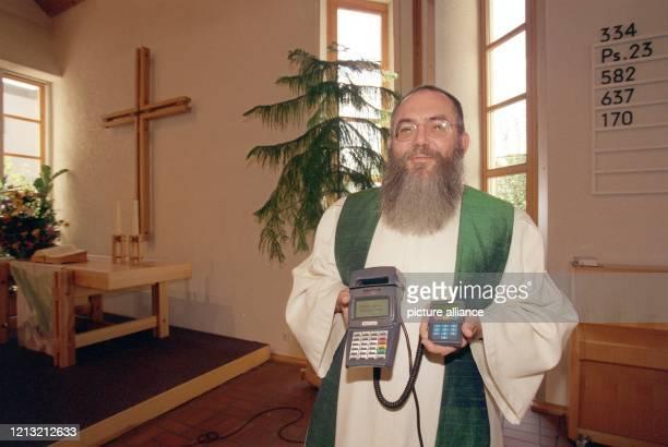 Pfarrer GerritWillem Obermann von der PetrusKirche in Bernhausen bei Stuttgart präsentiert am 2191998 im Kirchenraum ein elektronisches Terminal für...