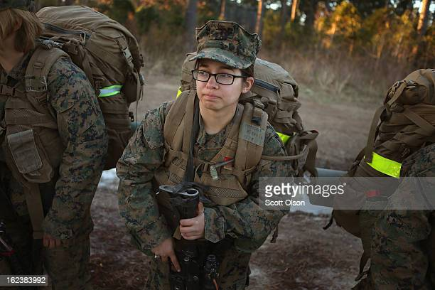 Pfc Amanda Patterson of Detroit Michigan prepares to head out with other male and female Marines on a 15 kilometer night hike carrying a 55 pound...
