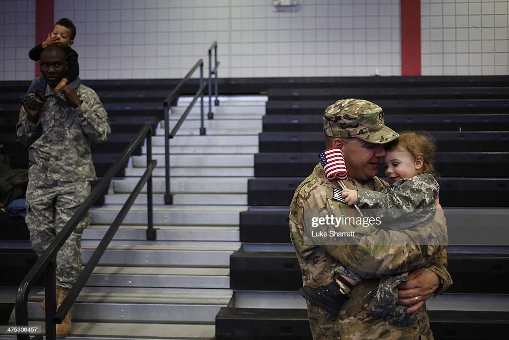 Pfc. Brian Lang of the U.S. Army's 3rd Brigade Combat Team, 1st Infantry Division, holds his son Johnathan Lang, 2, following a homecoming ceremony in the Natcher Physical Fitness Center on Fort Knox on Thursday, February 27, 2014 in Fort Knox, Ky. About 100 soldiers returned to Fort Knox after a nine-month combat deployment conducting village stability operations and working alongside Afghan military and police forces.