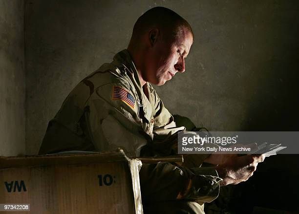 Pfc. Derek Garrity of the Army's 82nd Airborne Division, who is from Queens, N.Y., looks at photos sent to him by his mother at Forward Operating...